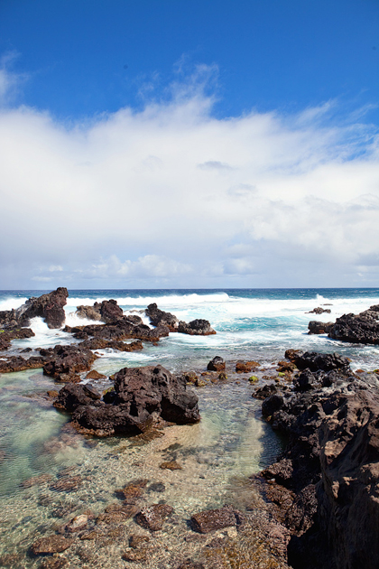 Volcanic rock dots Paia Bay, a popular surf spot on Maui