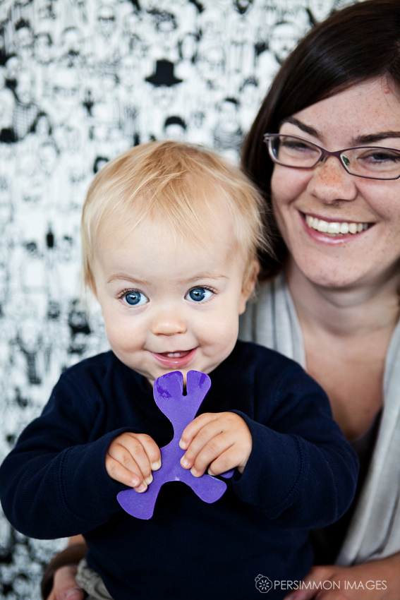 Liam smiles for the photographer as he munches a purple building toy while mom watches