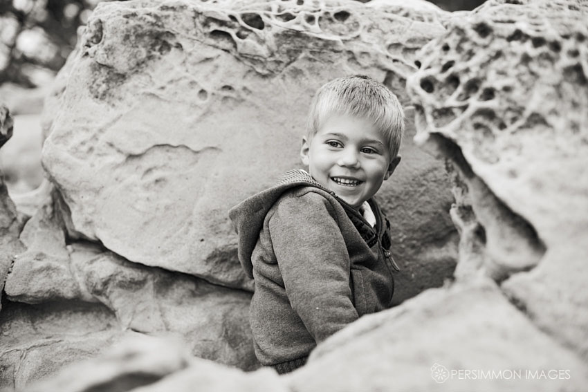 Child portrait of little boy peeking out from California beach rocks toward the photographer