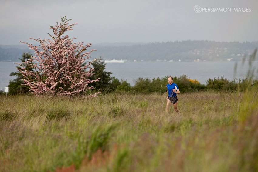 Seattle sports photographer Kat Speyer captures runner Anthony Targan in front of the Puget Sound with a ferry in the background