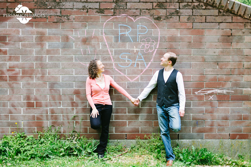 Modern engagement photography by Seattle wedding photographer Persimmon Images. Sidewalk chalk heart love at Volunteer Park band shell on Capitol Hill