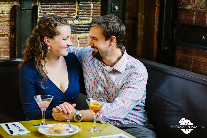 Seattle bar engagement photography at Cafe Presse on Capitol Hill. Candid engagement photography of couple sharing cocktails by Persimmon Images